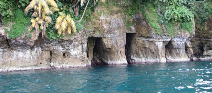 Ein Bootsausflug auf den Bocas del Torros Inseln: Man sieht Felsen mit einem Höhleneingang im Meer