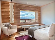Ein Zimmer des Tierra Patagonia Hotel in Chile: Stilvoll eingerichtet mit Holzboden und Fenster mit Panoramablick