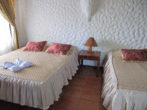 Die Austattung eines Standard-Zimmers in der Lagarta Lodge: Zwei Bettern in einem rustikalen Ambiente mit Fliesenboden und verzeirter Wand
