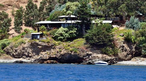 Blick vom Boot aus auf die Robinson Crusoe Lodge, die an einem Felshang liegt.