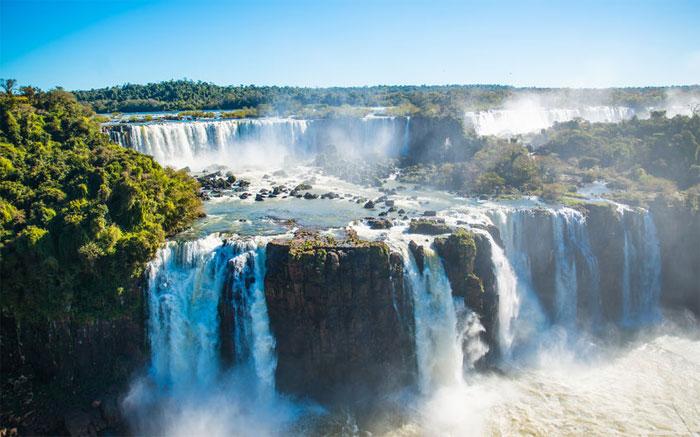 Man sieht die Iguazu Wasserfälle (falls) von oben bei blauem Himmel