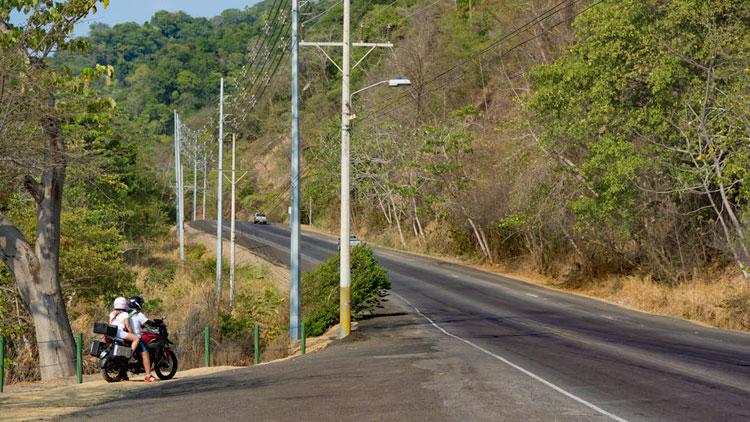 Man sieht eine Landstraße. Aus einer Einfahrt möchte ein Motorrad einbiegen.