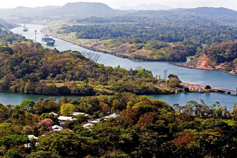 Blick über den Panama Kanal, der in eine grüne und bewaldete Hügellandschaft eingebettet ist.